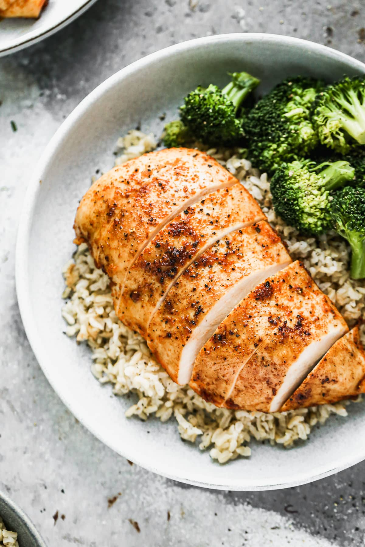 A chicken breast served on a bowl of rice and broccoli