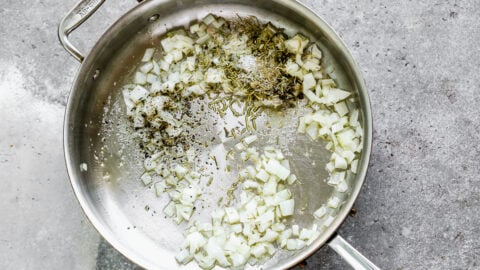 Onion , herbs, and spices in a pot
