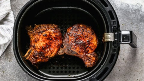Two pork chops in an air fryer