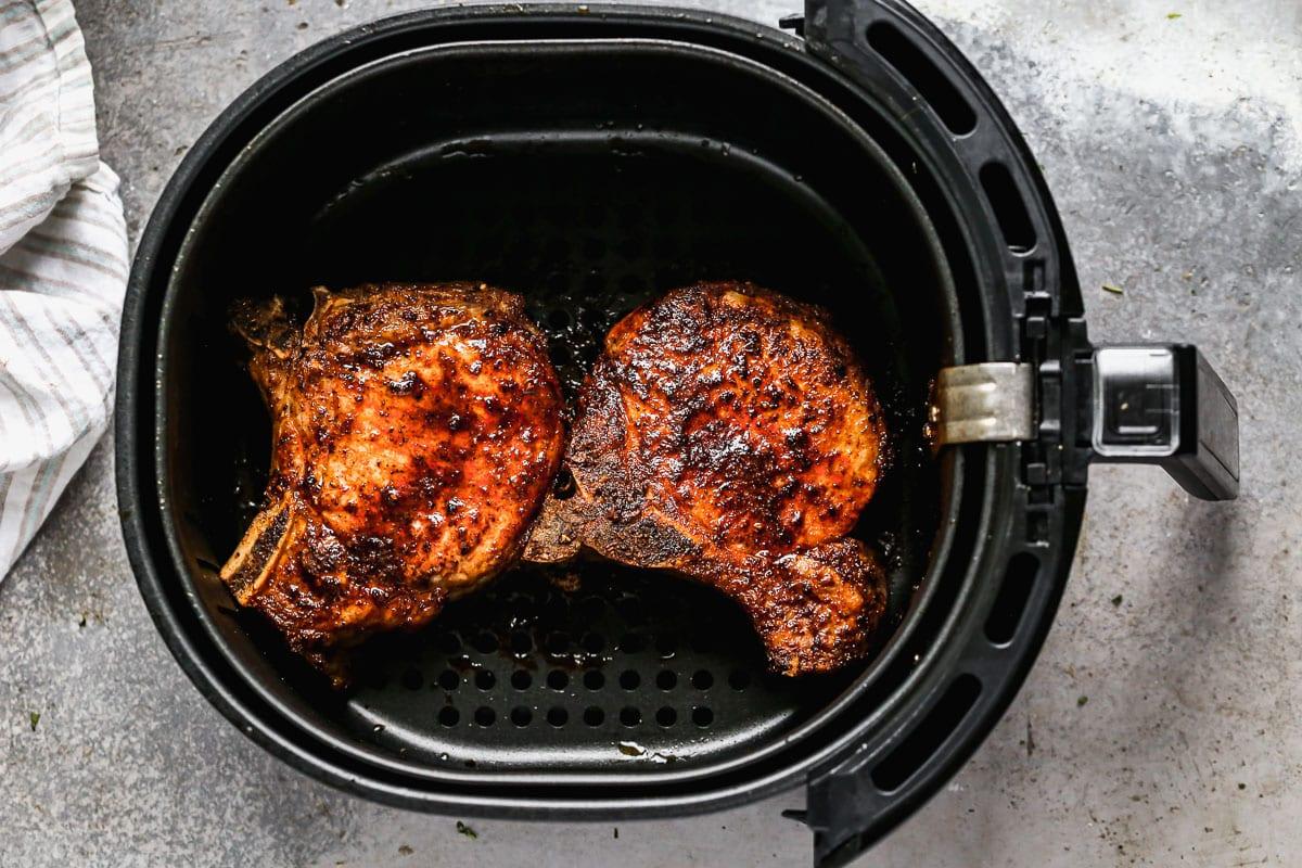 Two pork chops in an air fryer
