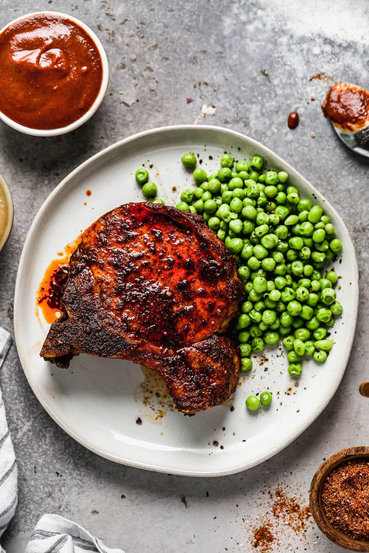 An air fryer pork chop with sauce and peas