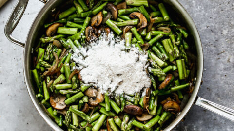 Flour added to a skillet of mushrooms and asparagus