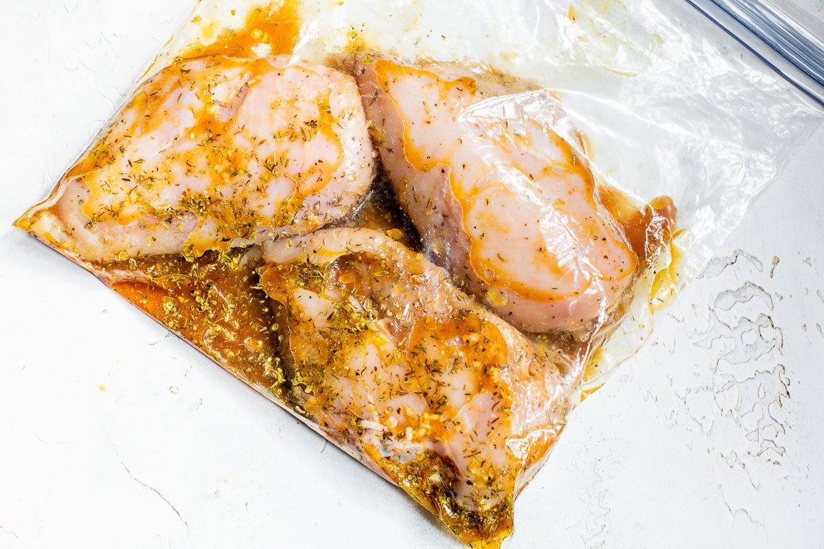 Three chicken breasts in a bag of chicken marinade