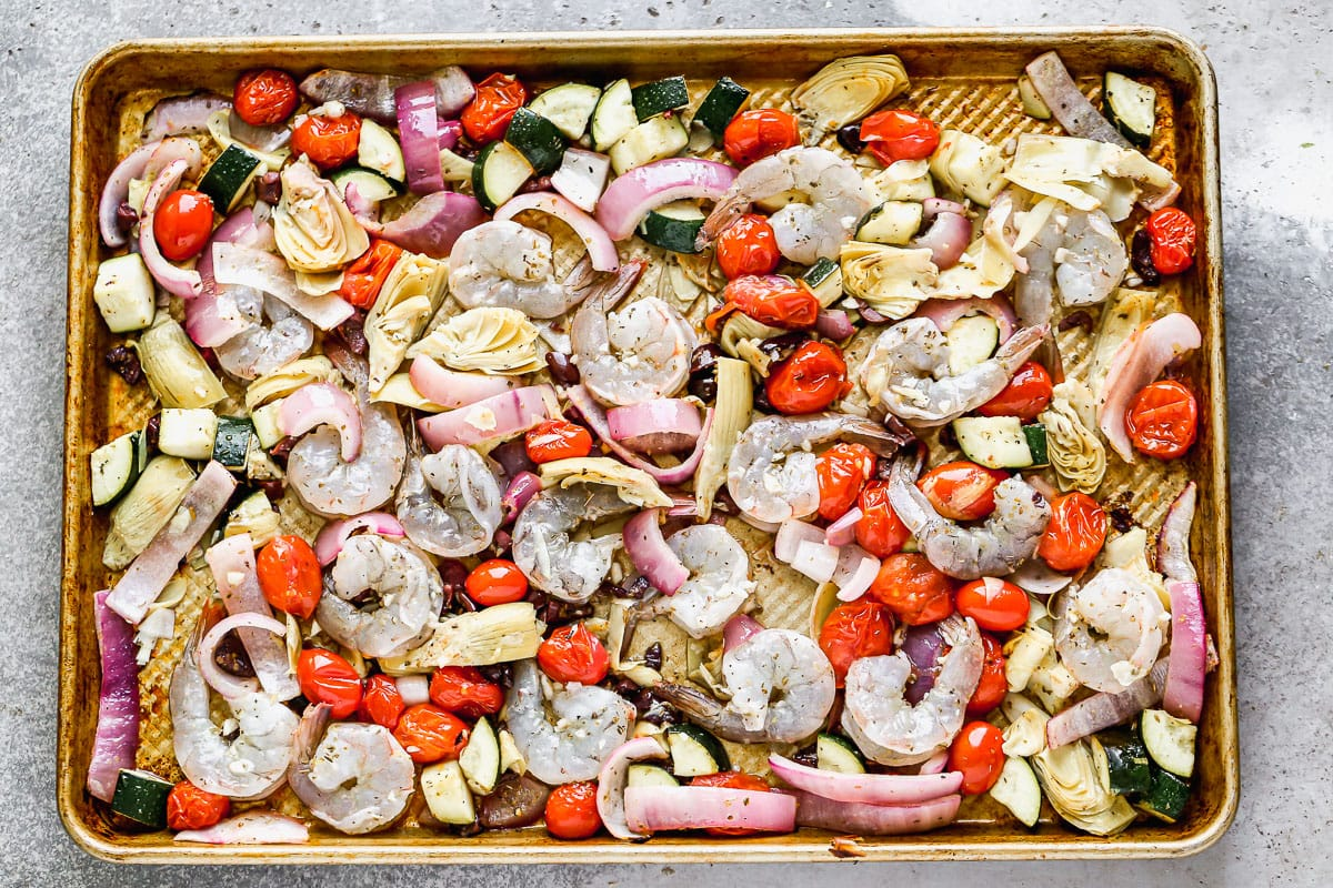 Raw shrimp and vegetables on a sheet pan