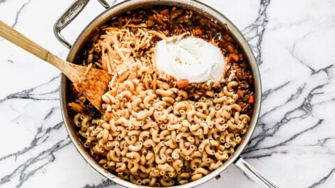 Cheese, yogurt, and pasta being added to a skillet