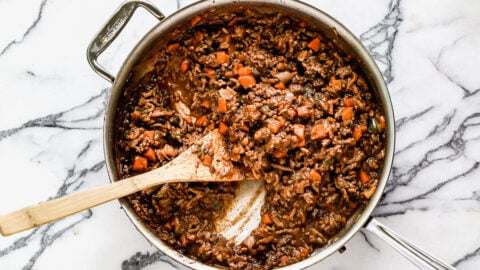 Hamburger casserole in a skillet with a wooden spoon
