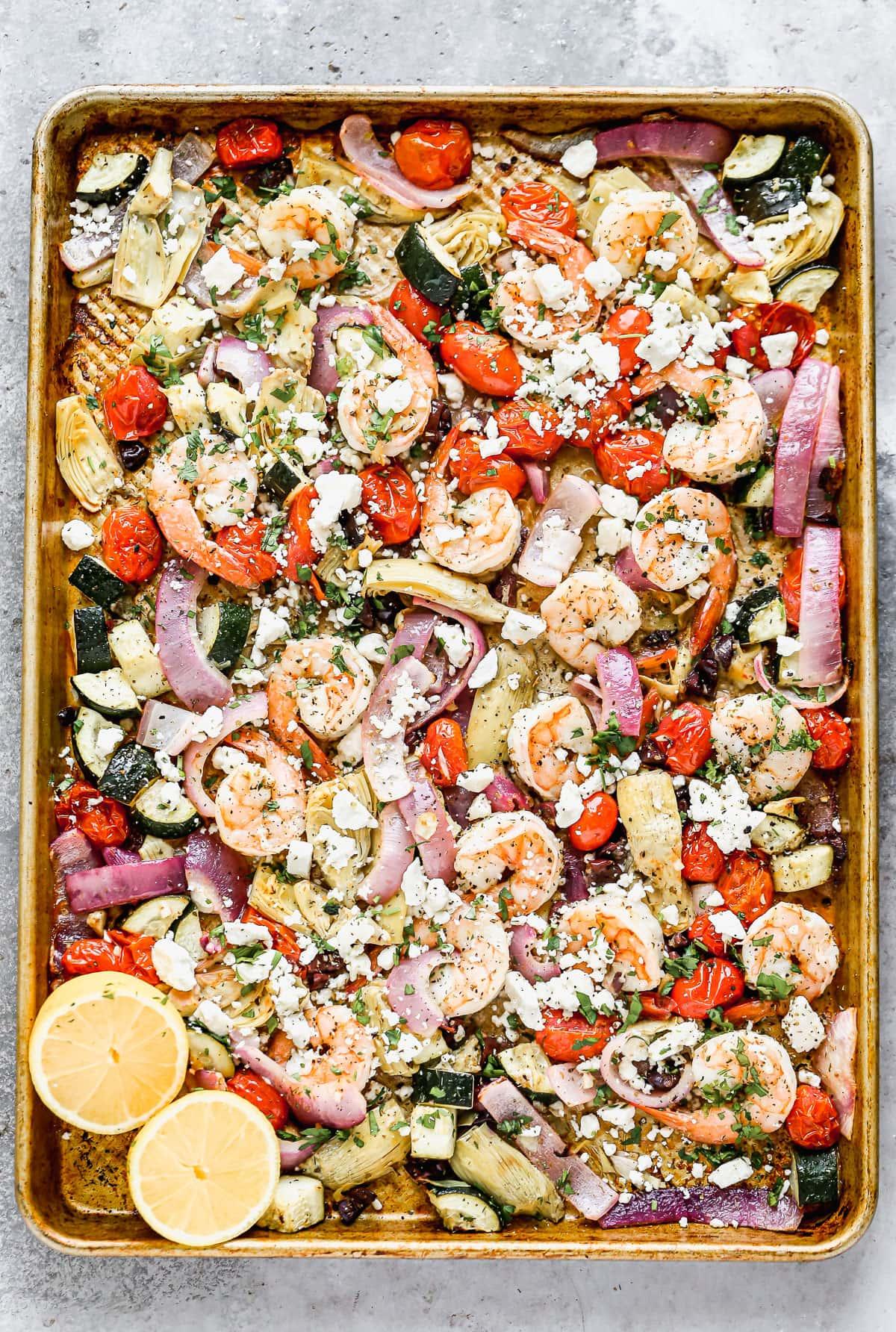 Camarones, verduras y queso en una bandeja para hornear.