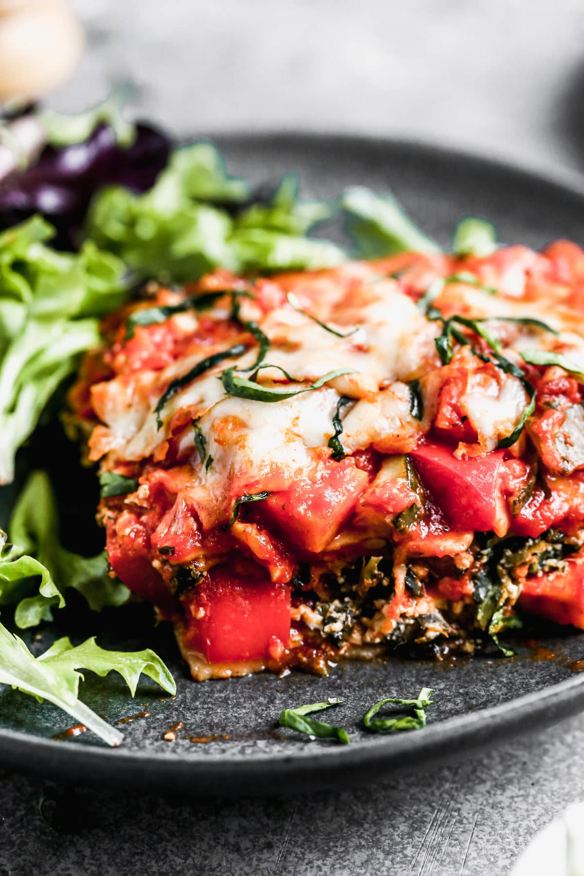 A plate with salad and vegetable lasagna