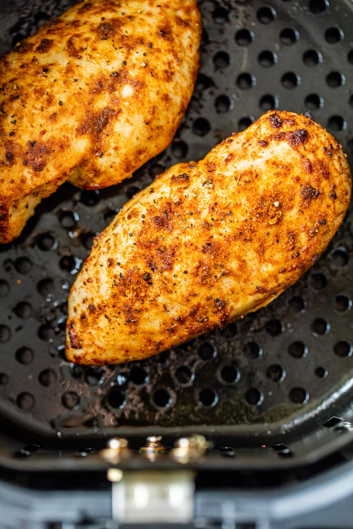 Two air fryer chicken breasts with seasoning