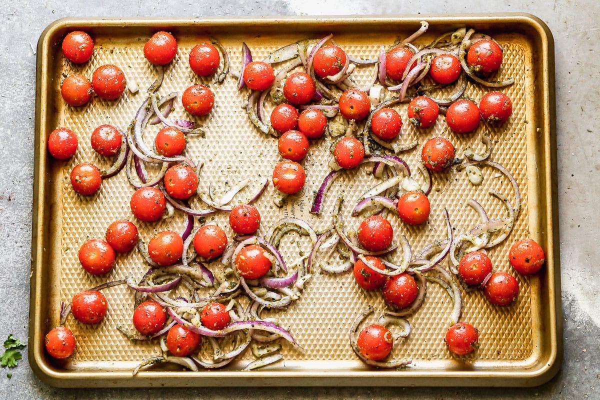 Tomates y cebollas en una bandeja para hornear.