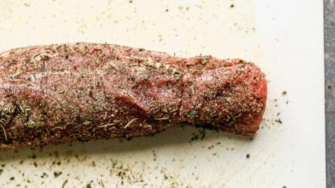 A seasoned pork tenderloin on a cutting board