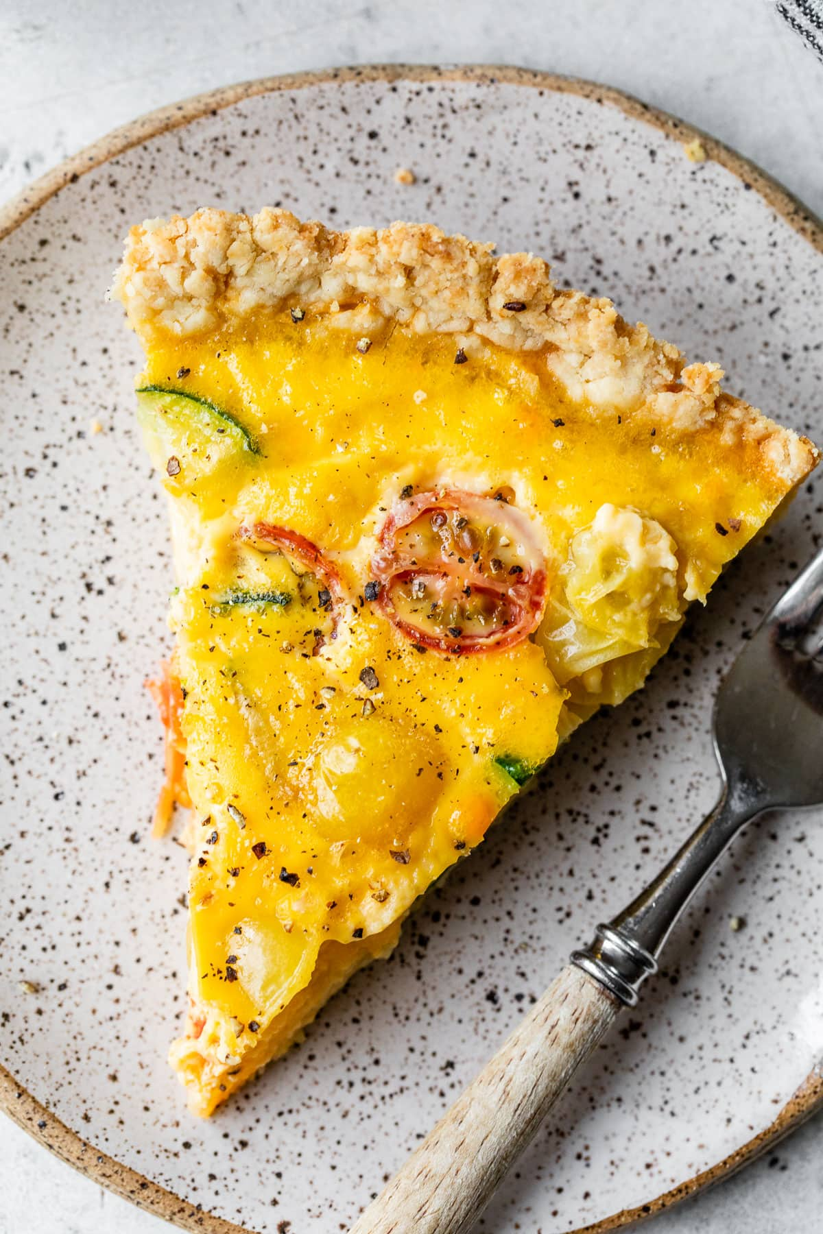 A slice of quiche on a plate