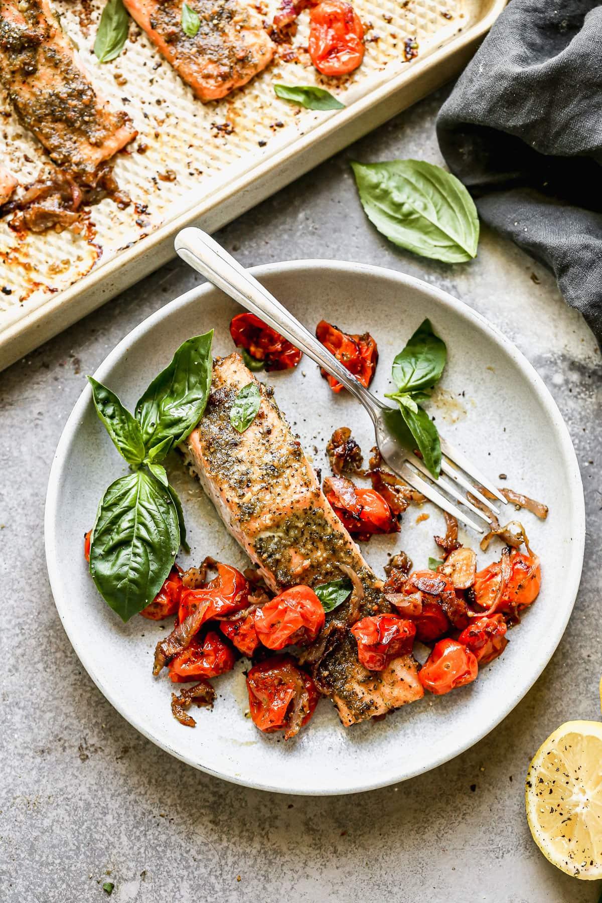 Salmón con pesto, tomate y albahaca en un plato
