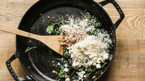 Cheese, walnuts, and spinach in a skillet