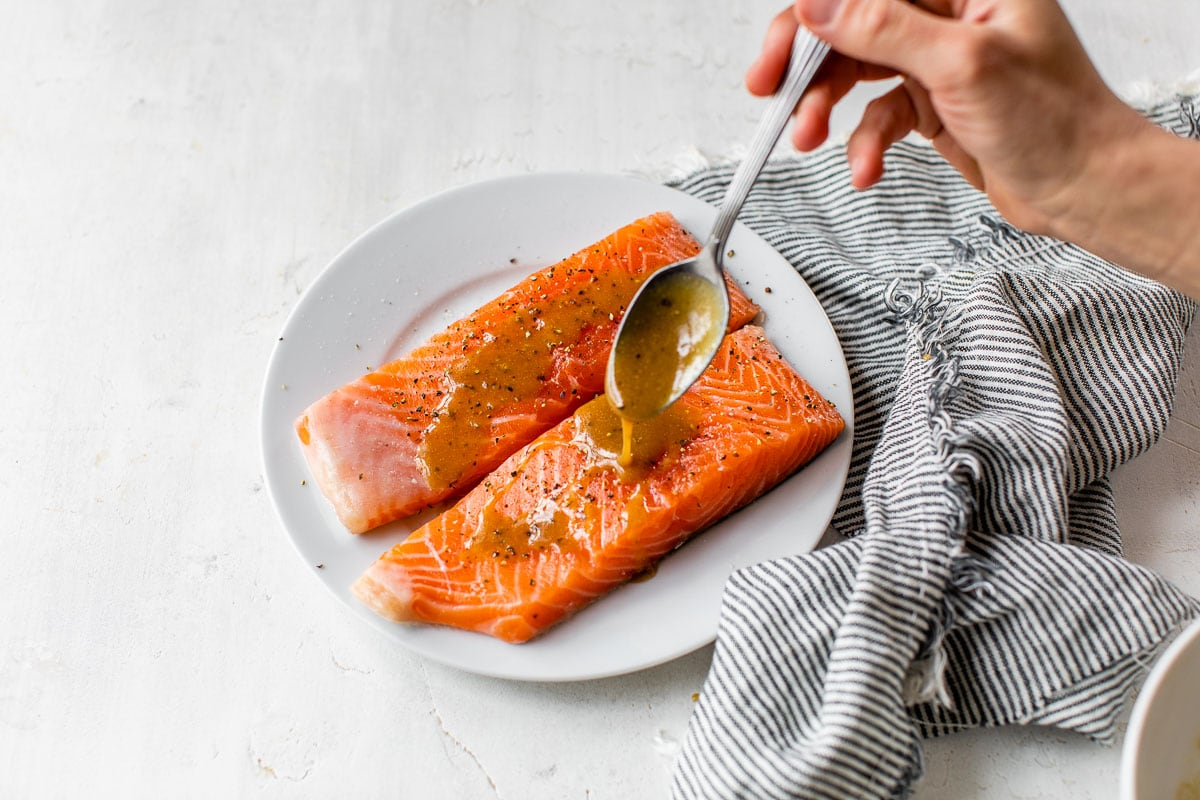 Sauce being drizzled over salmon