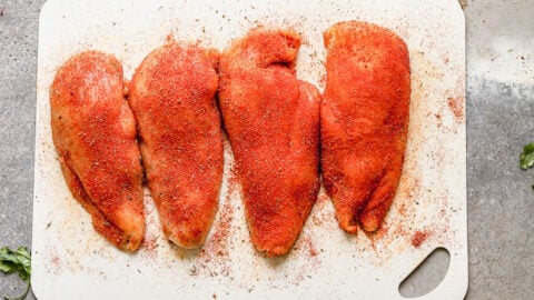 Four chicken breasts covered in spices