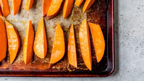 Unbaked sweet potato wedges on a baking sheet