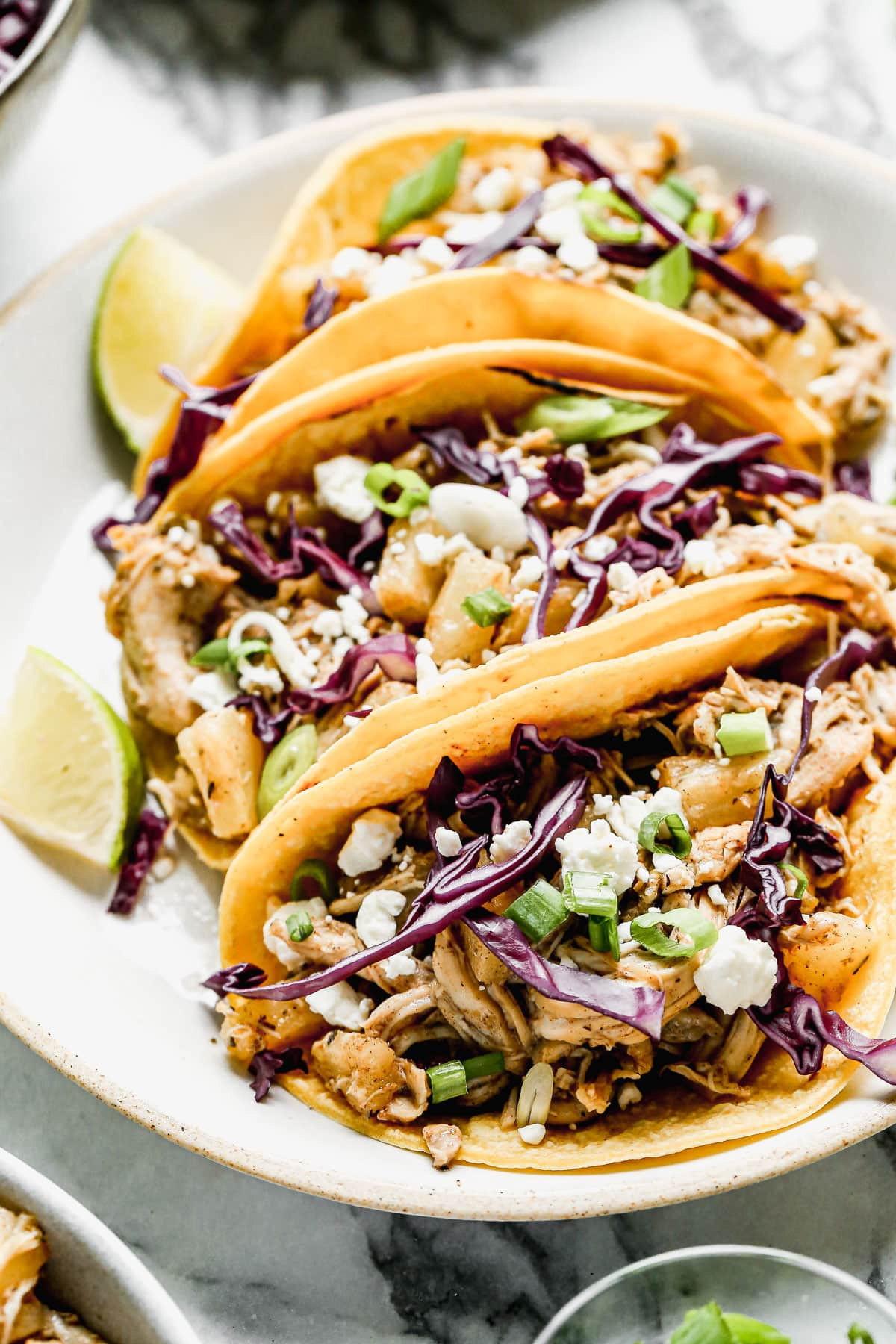 A plate of jerk chicken tacos with lime