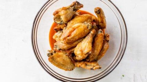 mix buffalo sauce on crispy chicken wings