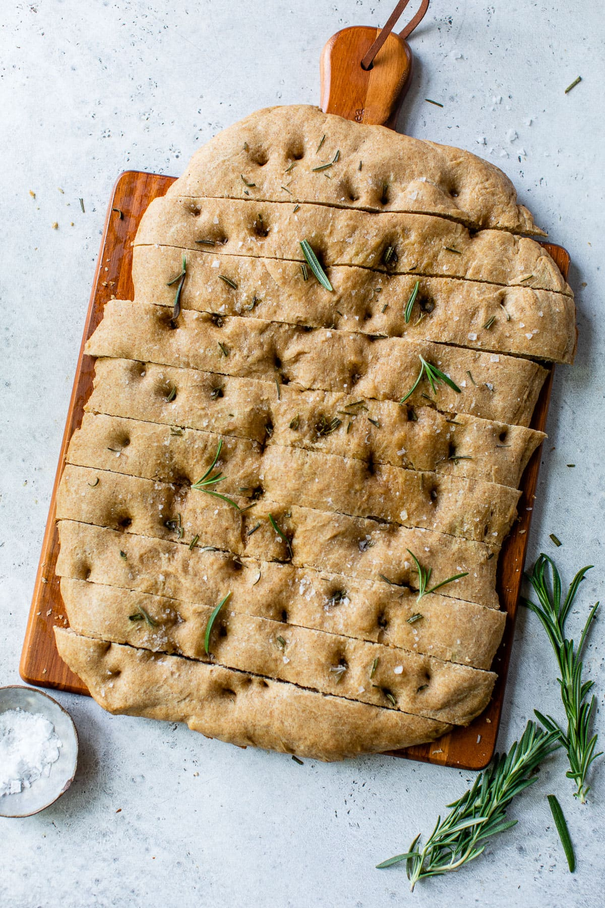 sliced no knead focaccia made with whole wheat flour on a wood serving board