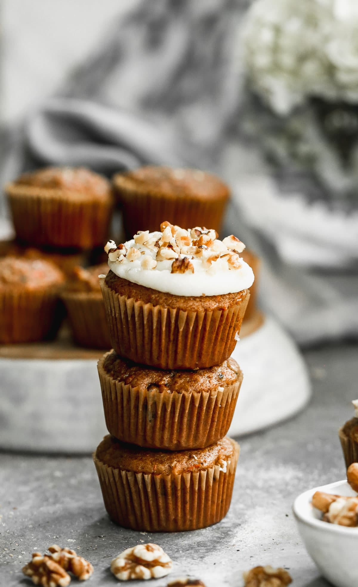 A stack of loaded carrot cupcakes with cream cheese frosting