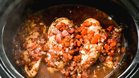 raw chicken with balsamic tomato sauce in a crockpot ready to cook