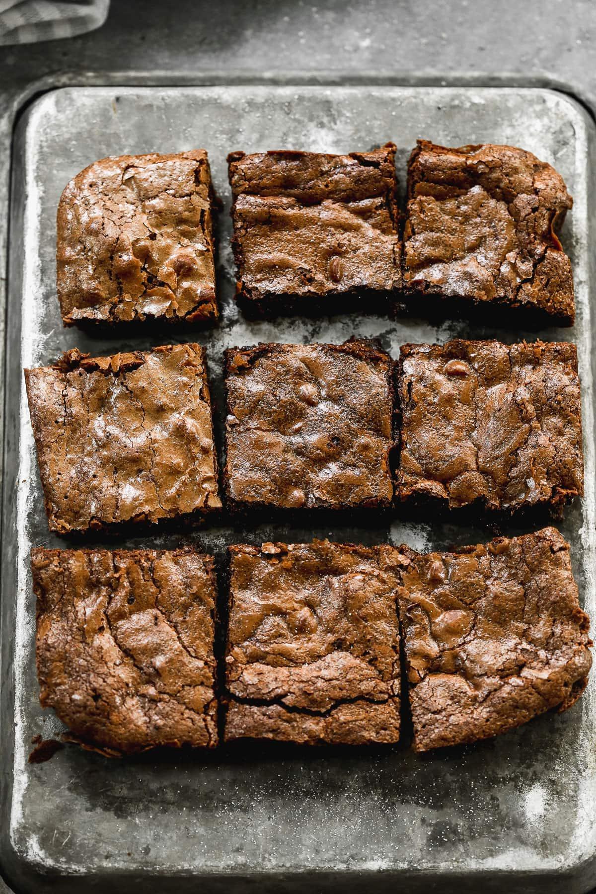 dense chocolate brownies cut into squares on baking sheet