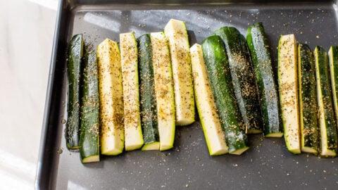 zucchini with seasoning on a pan