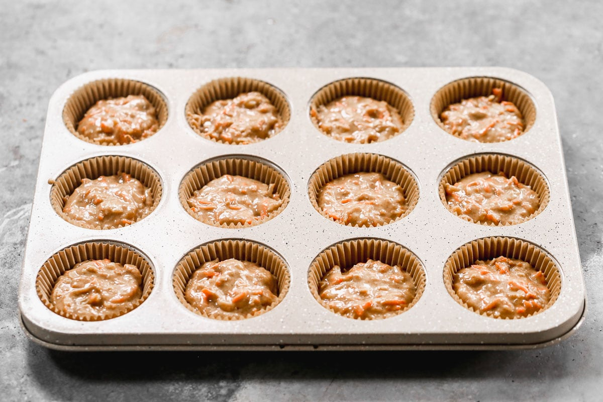 a muffin tin lined and filled with classic carrot cake batter