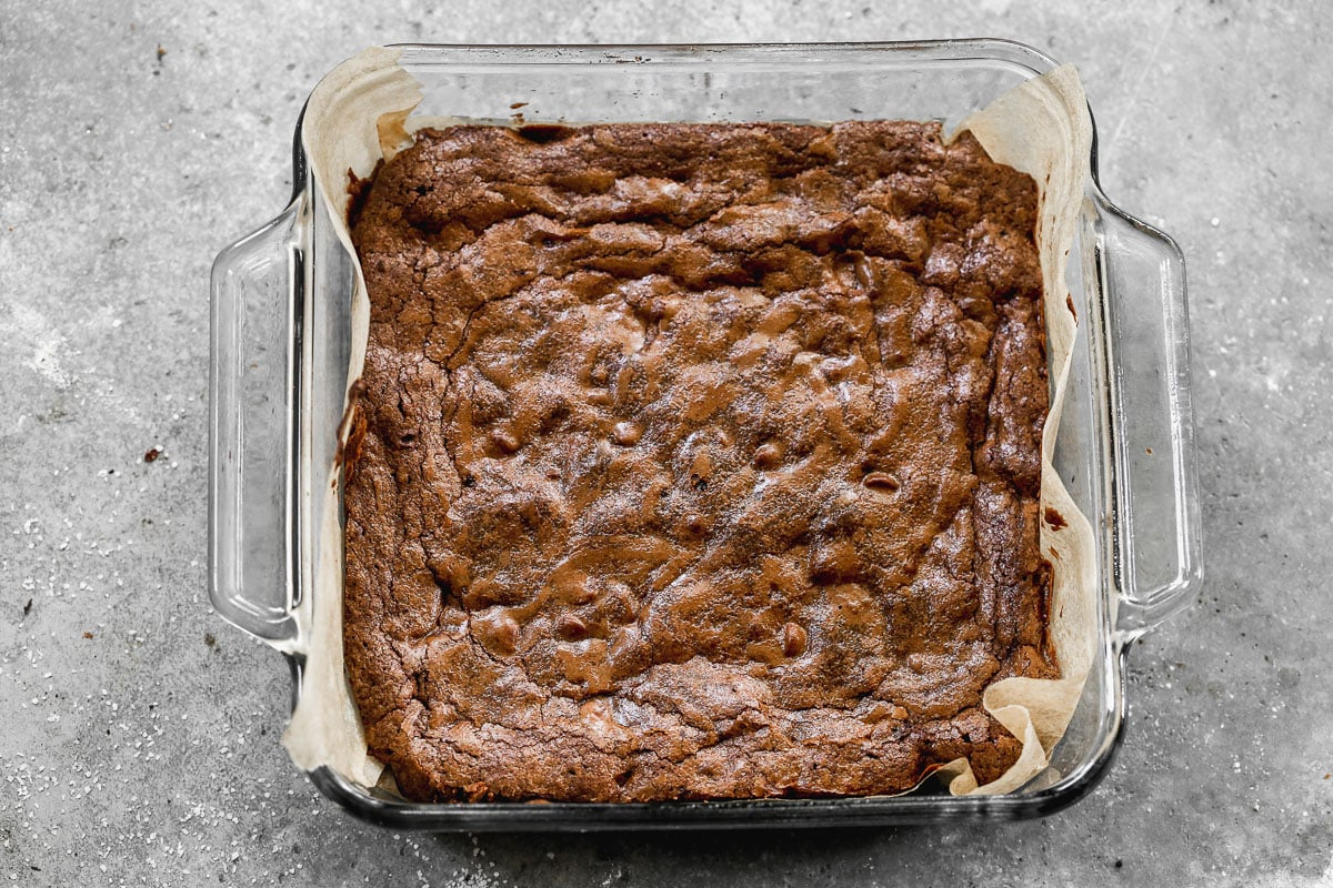 freshly baked one bowl brownies in an 8x8 glass pan lined with parchment paper