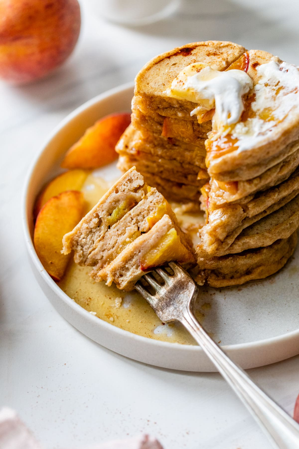 a stack of fluffy peach pancakes with a bite cut on a fork