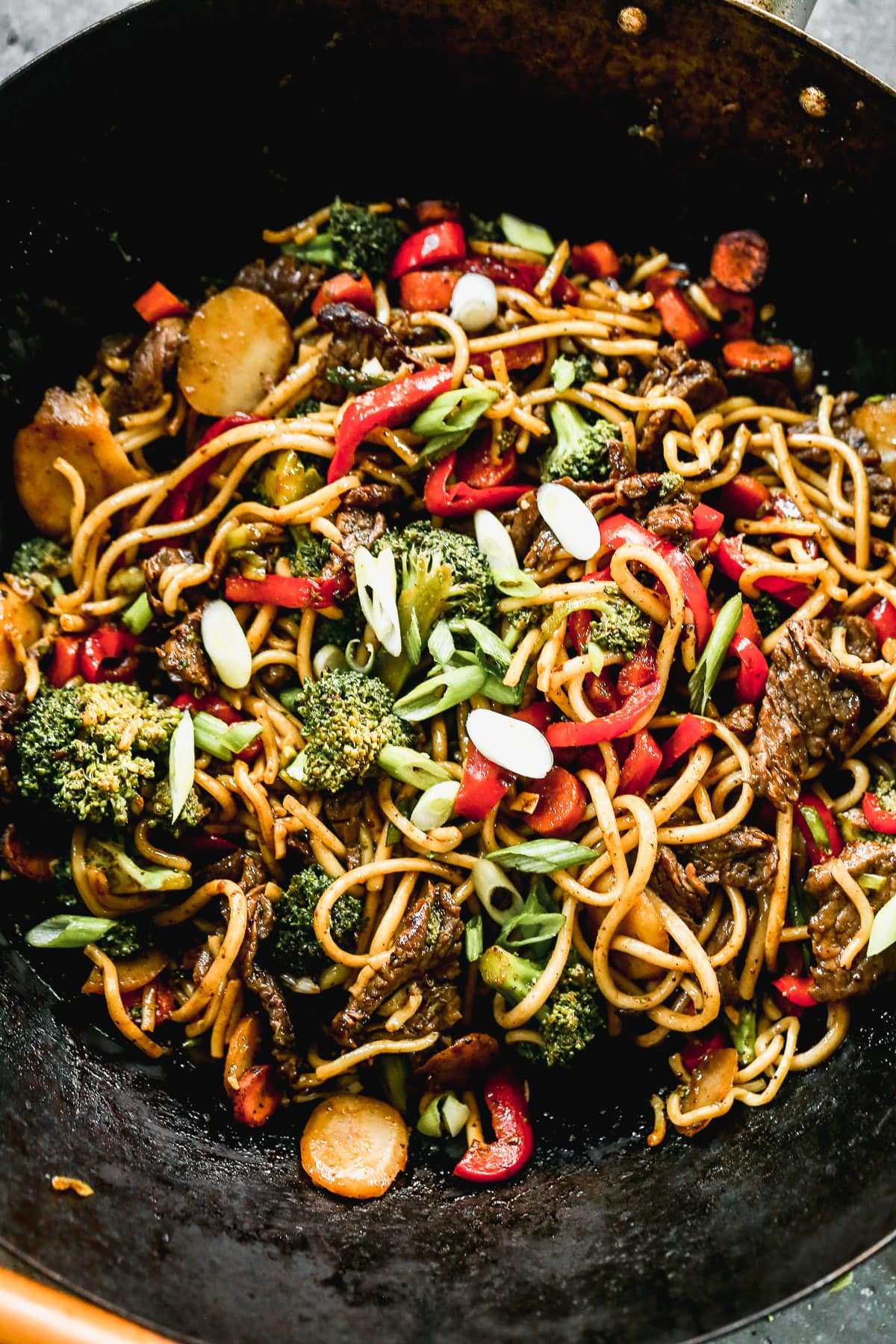 beef lo mein and vegetables cooking in skillet