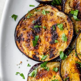 grilled eggplant medallions on a plate with oil and seasoning