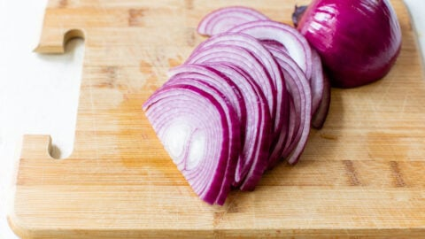slices of red onion for pickling on a cutting board