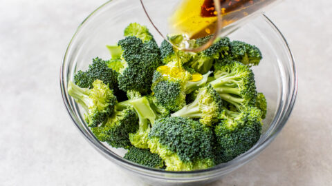 pouring sauce on chopped broccoli in a bowl