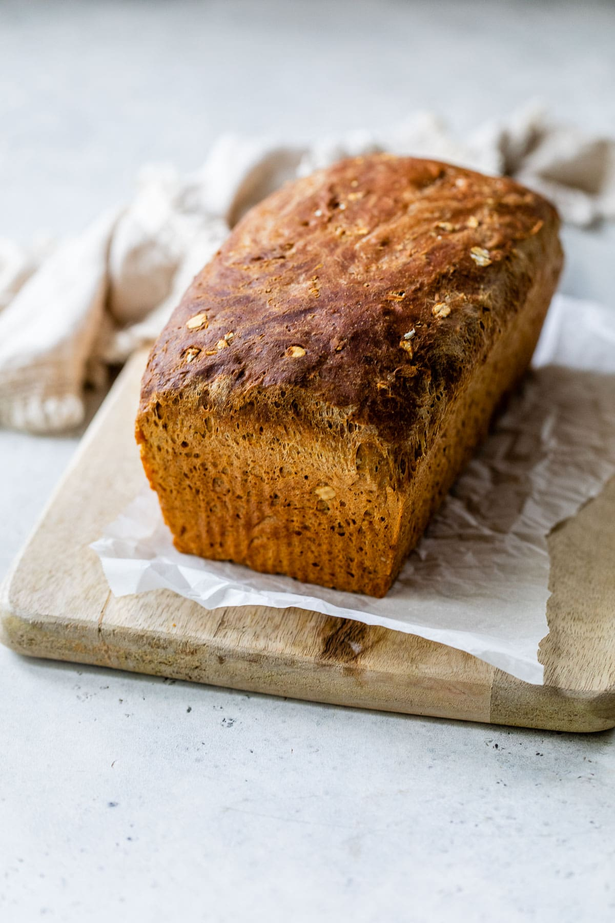 a whole loaf of golden old fashioned oatmeal bread made with molasses on a cutting board with parchment paper