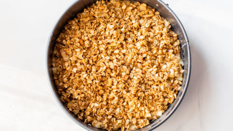Unbaked apple coffee cake in a springform pan topped with streusel
