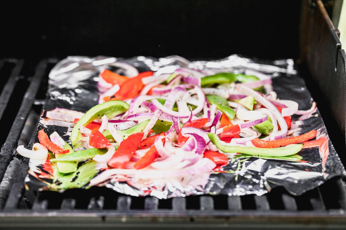 grilling peppers and onions on a piece of foil on a hot grill