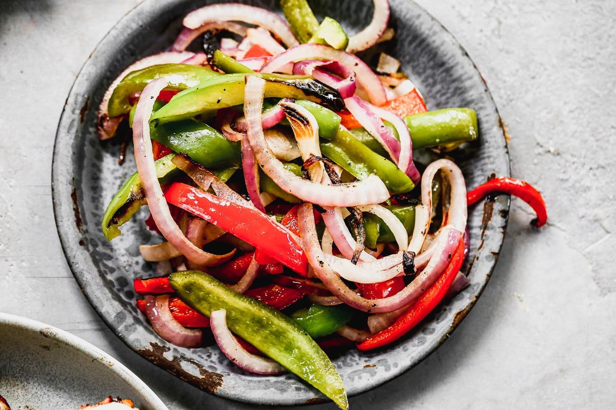 grilled peppers and onions on a stoneware plate