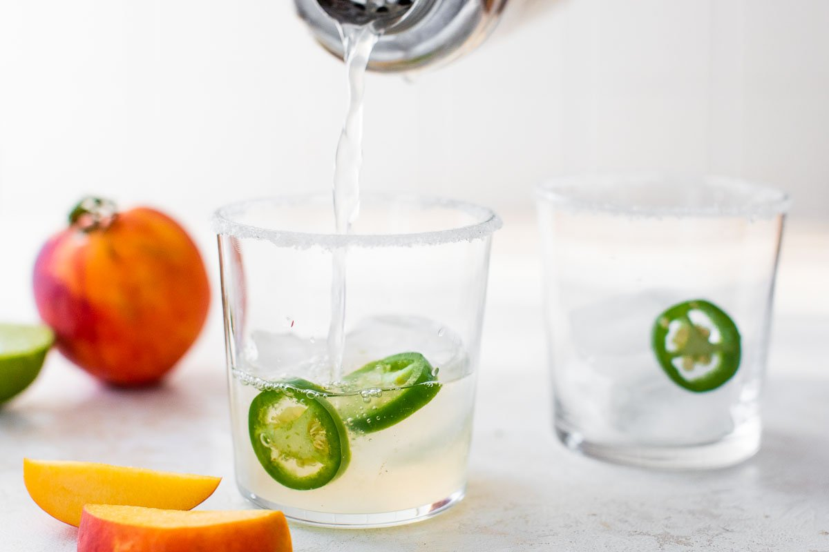 pouring peach margarita into a cocktail glass with sliced jalapenos
