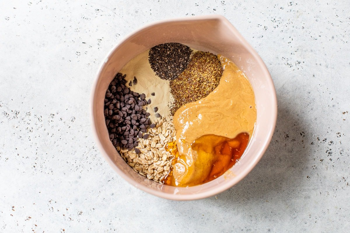 peanut butter, flaxseed, chia seeds, honey, oats and chocolate chips in a bowl