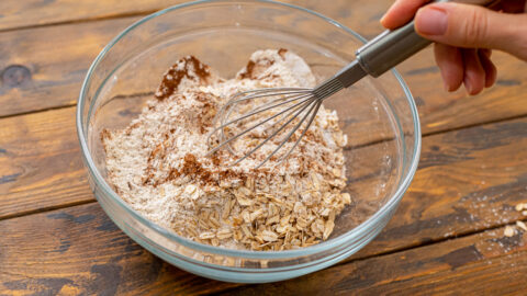 Combining dry ingredients together for pumpkin chocolate chip bread in a large mixing bowl