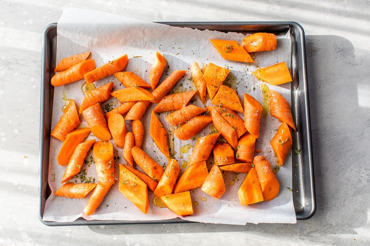 a sheet pan of carrots drizzled with olive oil and honey for roasting