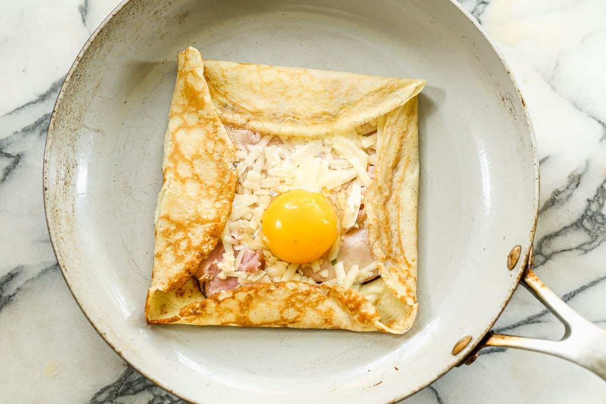 A savory crepe being made in a skillet