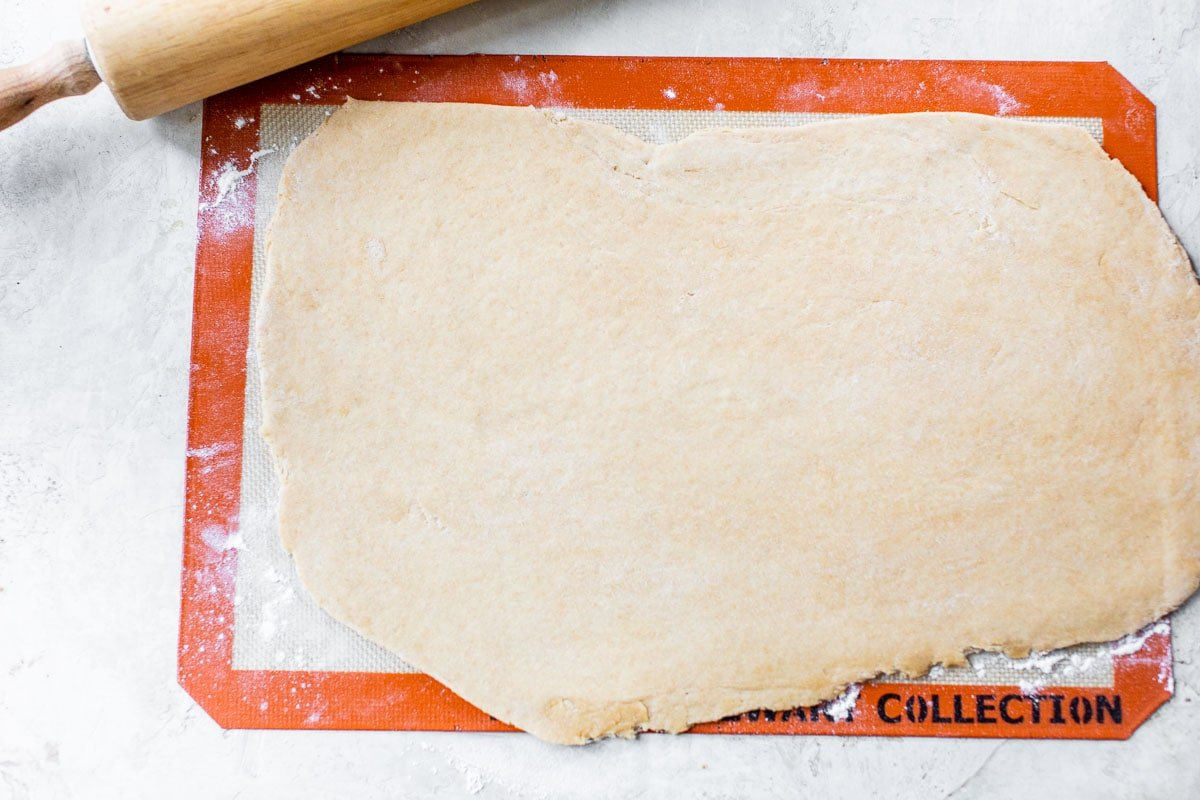 whole wheat pizza dough rolled out on a slip mat and ready for toppings