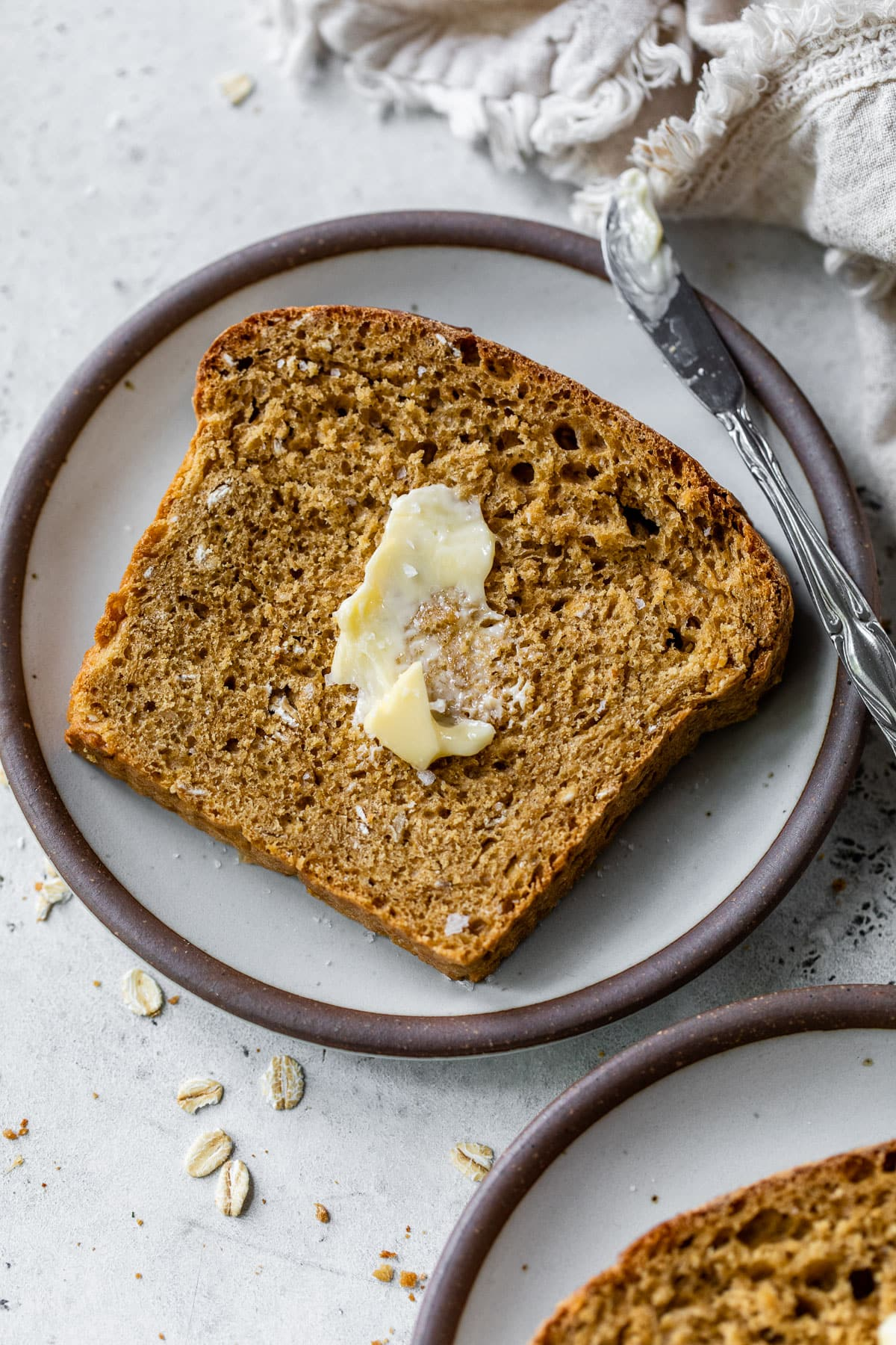 a slice of whole wheat oatmeal bread spread with butter