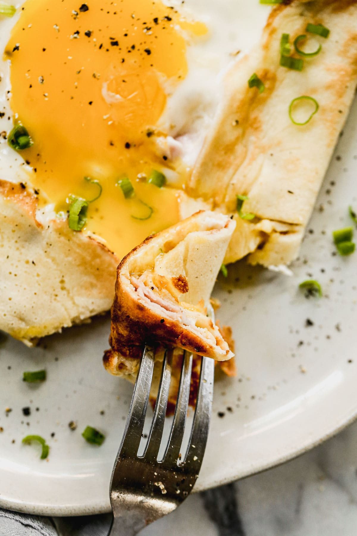 A bite of savory crepes on a fork