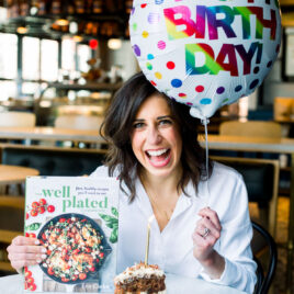 Erin Clarke with a slice of cake and a copy of The Well Plated Cookbook and a birthday balloon
