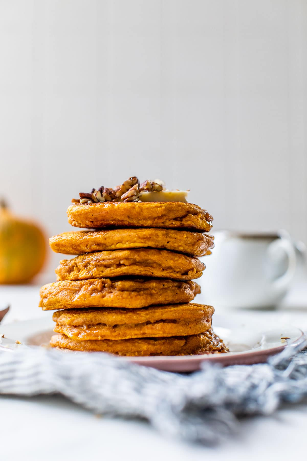 Healthy pumpkin pancakes with butter, maple syrup, and pecans