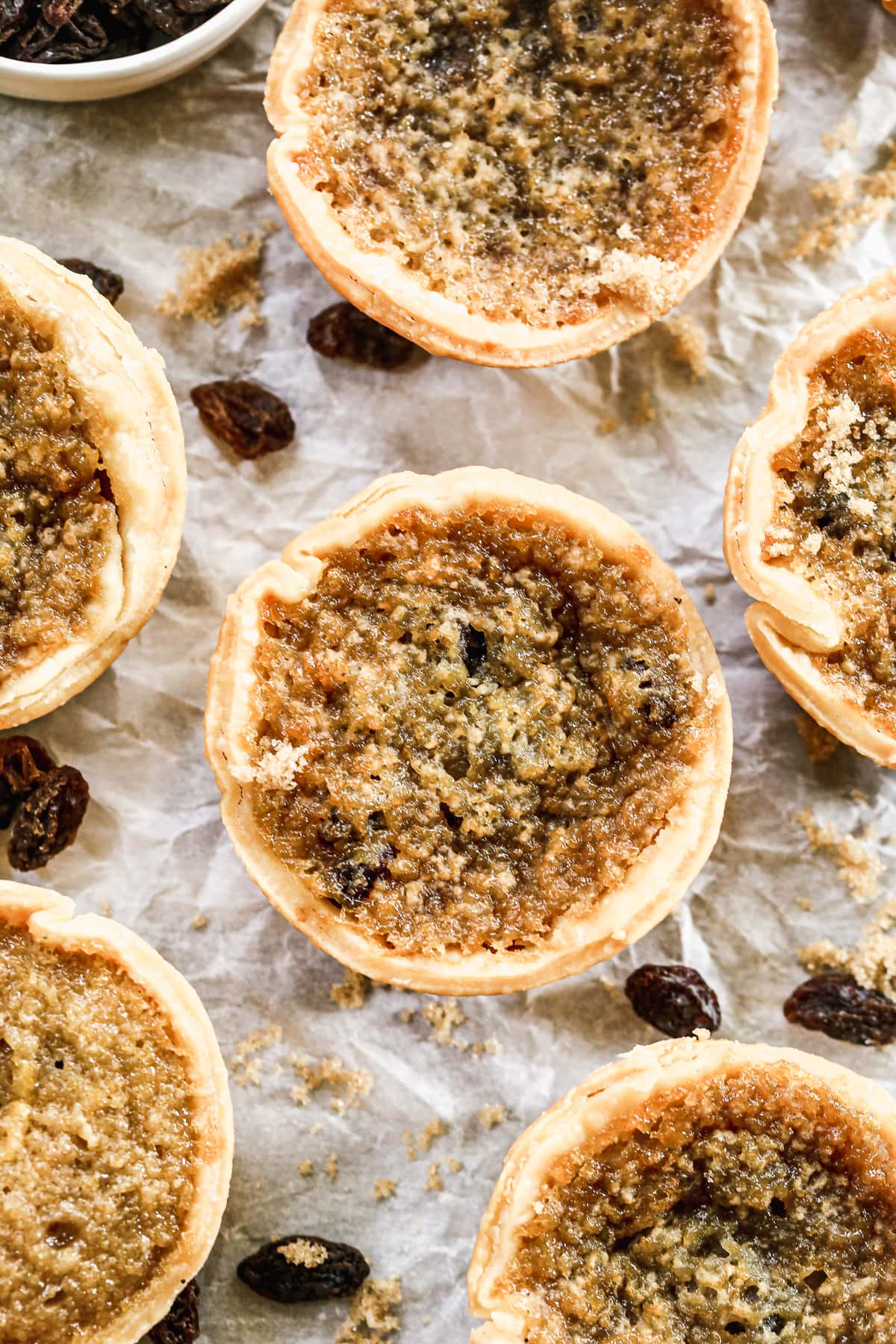 overhead photo of gooey Canadian butter tarts with raisins on parchment